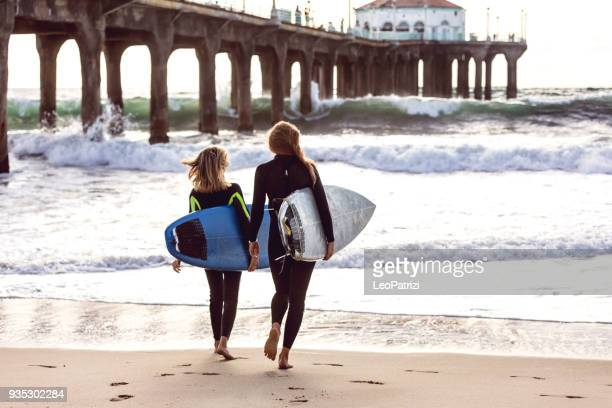 Women friends going to surf in Los Angeles - California