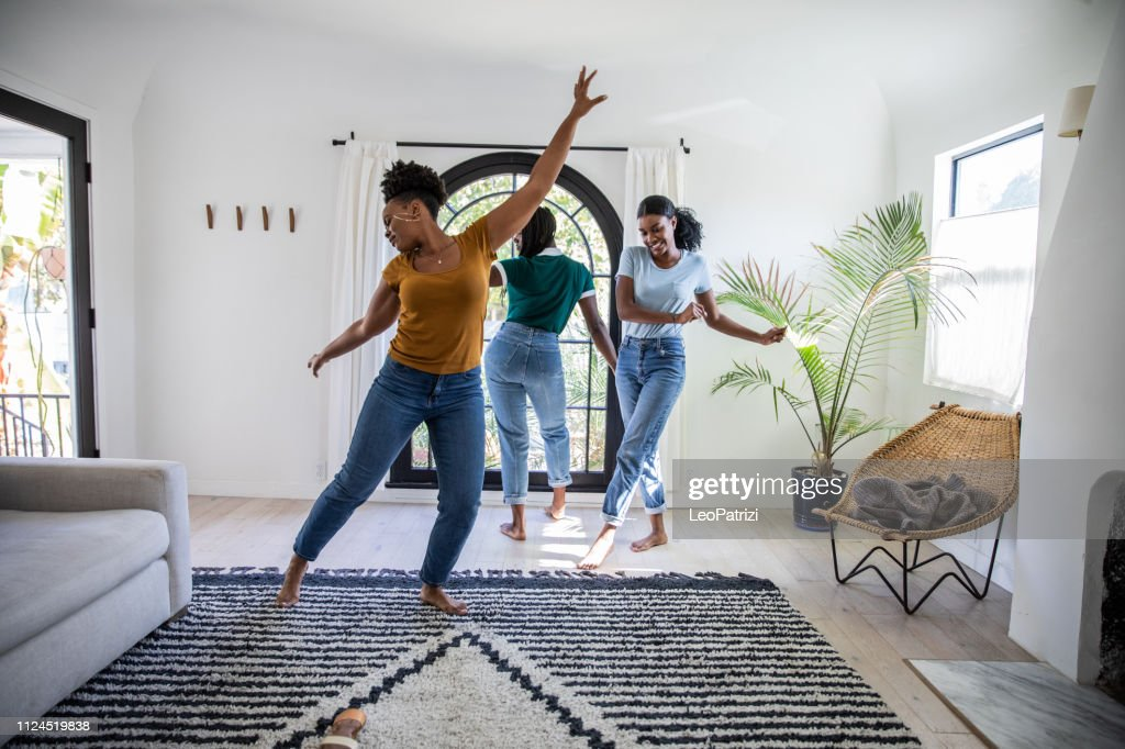 Women friends having fun at home dancing and singing in the living room : Stock Photo
