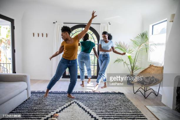 women friends having fun at home dancing and singing in the living room - dancing foto e immagini stock