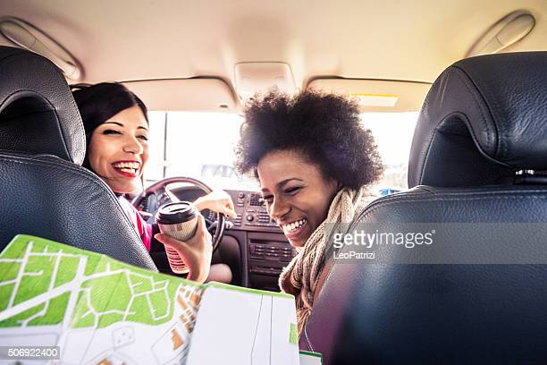 Women friends in the car looking the road map