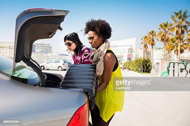 Femmes amis Chargement de la voiture de départ de vacances formidables