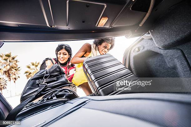 Women friends loading the car to start a great vacation