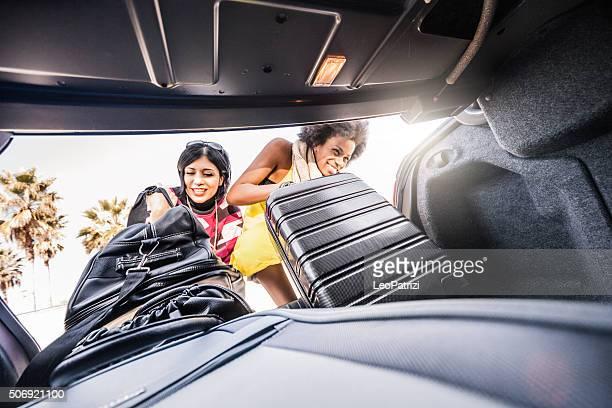 Mulheres amigos carregar o carro para iniciar uma grande cidade