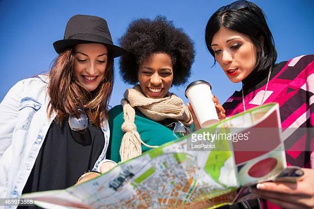 Femmes amis à la recherche dans la carte de la ville