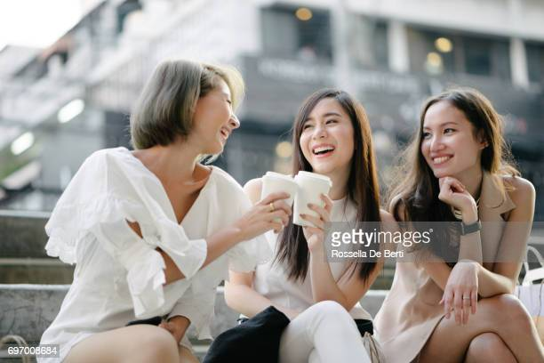 women friends out for shopping in bangkok city streets - asian drink stock photos and pictures