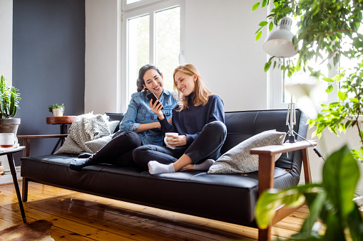 Women friends relaxing at home using smart phone - gettyimageskorea