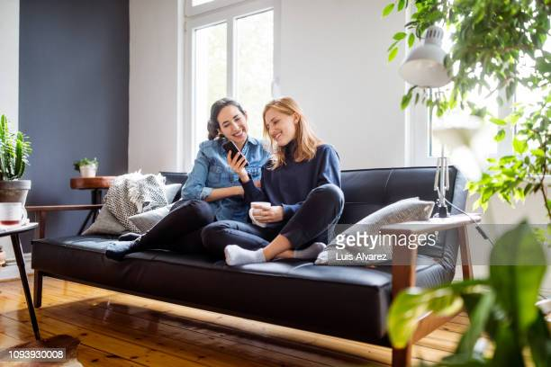 women friends relaxing at home using smart phone - sofa stock-fotos und bilder