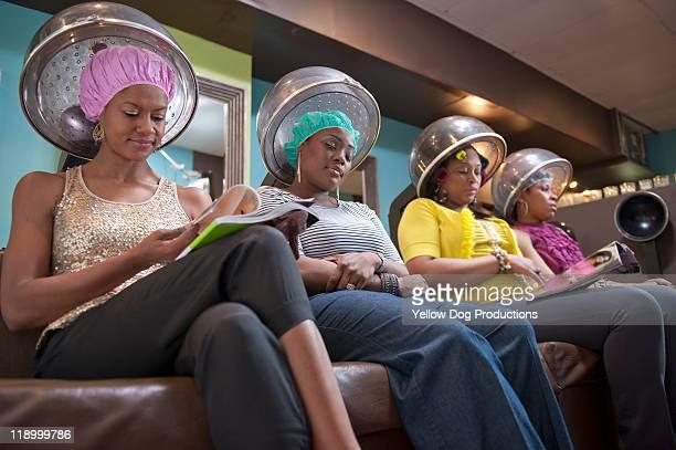 Women friends sitting under hair dryers at salon