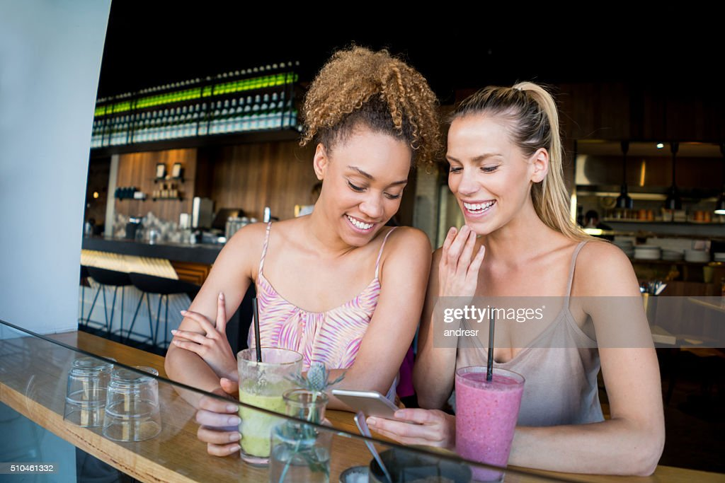 Women friends social networking at a cafe : Stock Photo