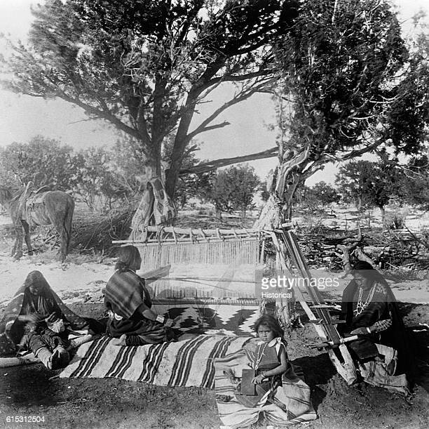 Women from a Navajo family weave blankets on a loom under a tree