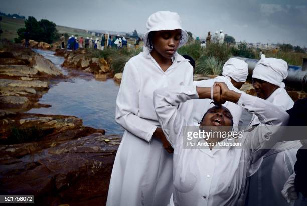 Women from Eastern Baptist Zionist Church pray during an outdoor service close to Orlando West in Soweto Johannesburg South Africa They celebrated...