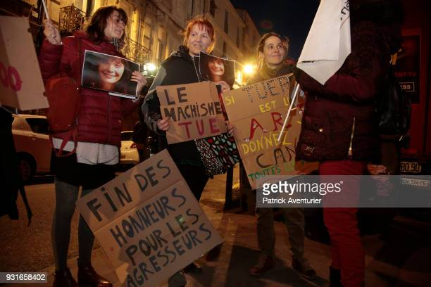 Women from feminist organizations holding photos of late French actress Marie Trintignant and placards reading 'If killing is an art award Cantat...