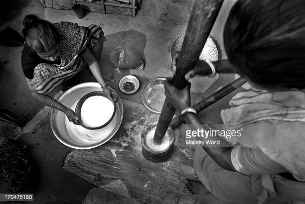 Women from Hindu community grinding rice for making cakes on Paus Shankranti festival at the end of Bangla month Paus Hindu workers do not go to work...