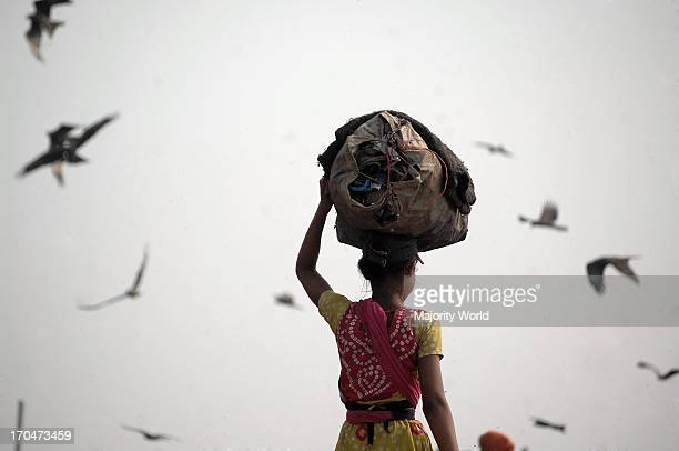 A women from indigent community collecting usable things for sale from a garbage pile in Matual Demra Dhaka Bangladesh February 6 2008