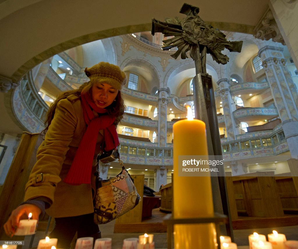 A women from Philippines stands next to the destroyed cross and lights a candle to commemorate the 68nd anniversary of the bombing of Dresden in the Frauenkirche (Church of Our Lady) on February 13, 2013 in Dresden, eastern Germany. A massive bombing raid by Allied forces on Dresden beginning on February 13, 1945 sparked a firestorm that destroyed much of the historical centre of the city. Later, a few thousand far-right extremists are expected to conduct a 'funeral march' through the city, opposed by thousands of anti-fascist activists who form a human chain as a sign against the neo-Nazis.