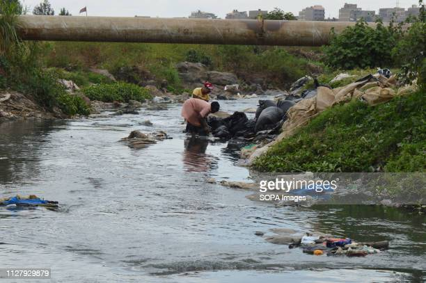 Women from sprawling slums of Dandora are seen washing sheets of plastic waste in the dirty waters of the River for recycling Nairobi generates an...
