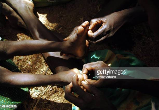 Women from Tama village pick thorns out of the feet of Ibrahim Abakar Ismael as he lies with his grandmother shortly after being picked up by the...