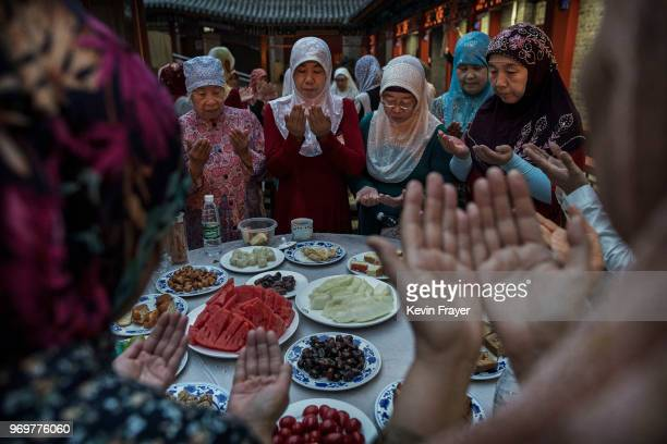Women from the Hui Muslim community pray over food before breaking their fast during the holy fasting month of Ramadan at the Nanxiapo Mosque on June...