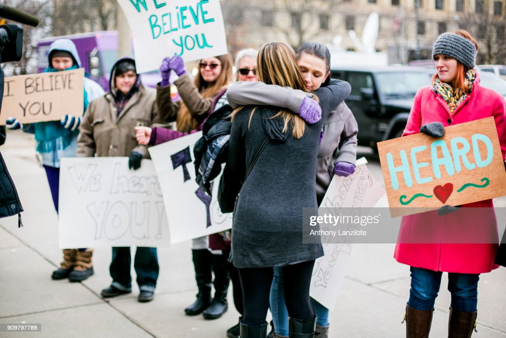 Women from the Michigan based victim advocacy groups End Violent Encounters and Firecracker Foundation cheer for women as they leave the courthouse after the sentencing of disgraced doctor Larry Nassar in Ingham County Circuit Court on January 24, 2018 in Lansing, Michigan. The former USA Gymnastics and Michigan State University doctor was sentenced to up to 175 years in prison for sexual assault after more than 150 women and girls confronted him in court and spoke of their abuse.