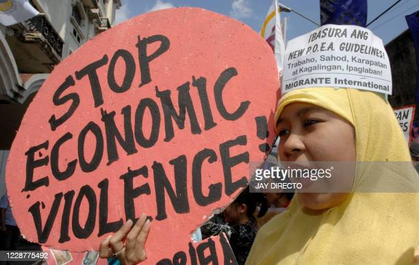 Women from the militant Gabriela organization in the Philippines carry a slogan denouncing the government's anti-women labor policies during a...