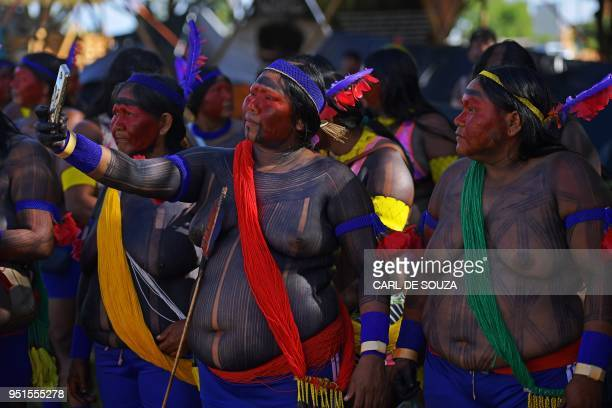 Women from the Xikrin tribe take selfies at the Acampamento Terra Livre in Brasilia on April 26 2018 Approximately 2500 indigenous people from...