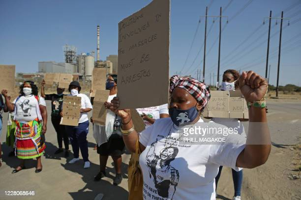 Women from Wonderkop informal settlement hold placards as they march to the koppie in Marikana near Rustenburg on August 16, 2020 where striking...