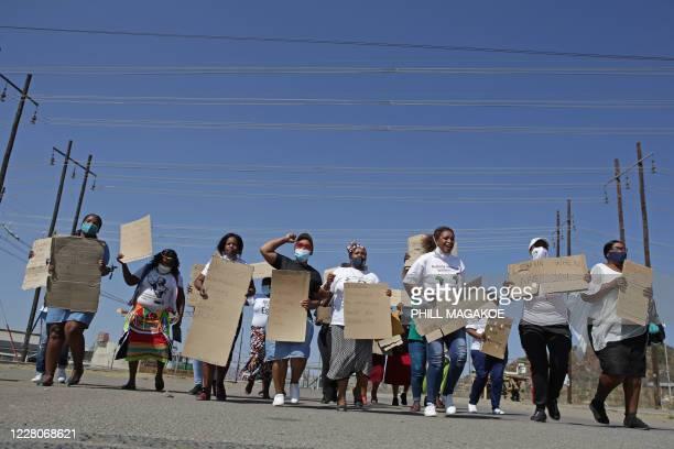 Women from Wonderkop informal settlement hold plackards as they march to the koppie in Marikana near Rustenburg on August 16, 2020 where striking...