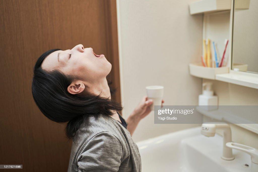 Women gargle with antivirus : Stock Photo