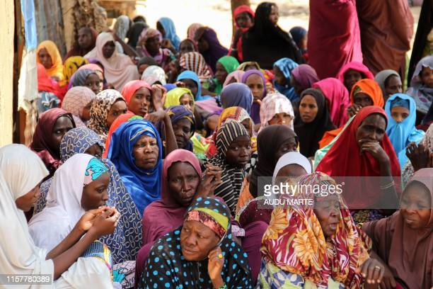 Women gather during a burial ceremony after two people were killed by Boko Haram fighters in Dalori camp for internally displaced people near...