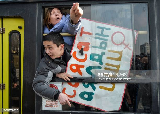 Women gestures from a police van after they were arrested while protesting against gender-based violence to mark International Women's Day in Bishkek...