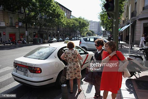 Women get out of a taxi near the affluent shopping street of Calle de Serrano on July 4 2012 in Madrid Spain Despite having the fourth largest...