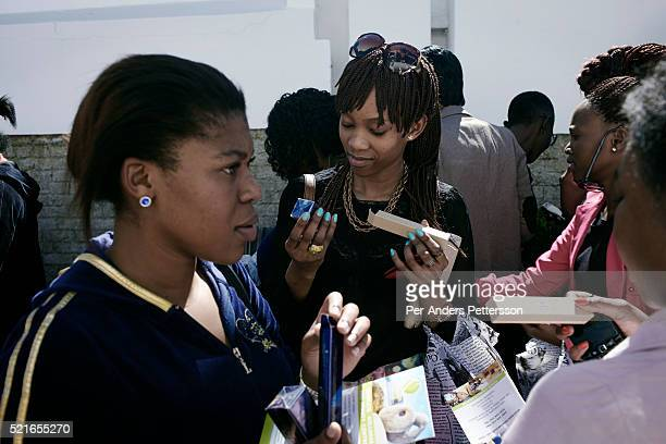 Women get samples of beauty products from a Estee Lauder while attending a market selling famous brand clothes on April 27 2013 in Soweto South...