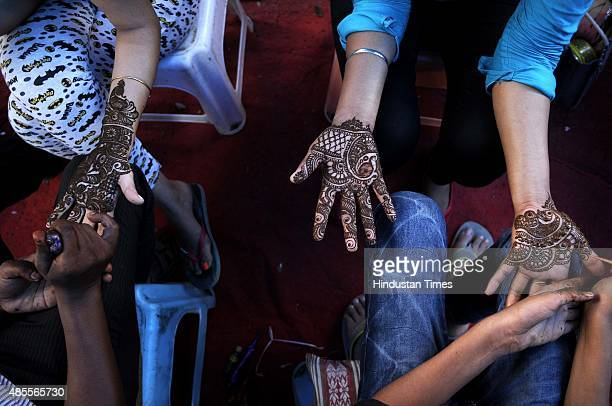 Women get their hands decorated with Henna along the roadside on the eve of Raksha Bandhan on August 28 2015 in Noida India Celebrating the bond...