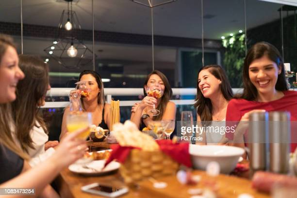 women get together to enjoy a friendly dinner - ladies' night stock pictures, royalty-free photos & images