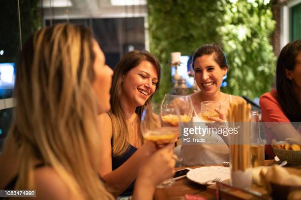 women get together to enjoy a friendly dinner - southern european descent stock pictures, royalty-free photos & images