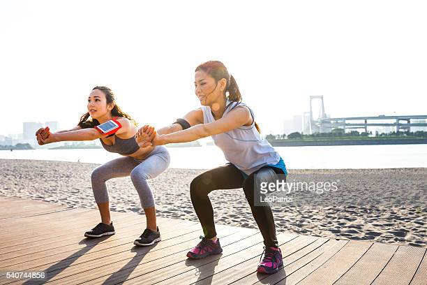 women getting fit in the city - tokyo - hurken stockfoto's en -beelden