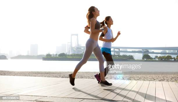 women getting fit taking run afterwork in tokyo - jogging stock pictures, royalty-free photos & images