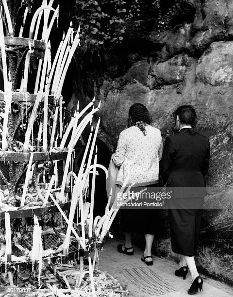 Women getting in the Grotto of Massabielle during the centenary of the apparitions of Our Lady to Saint Bernadette Soubirous Lourdes 22nd November...