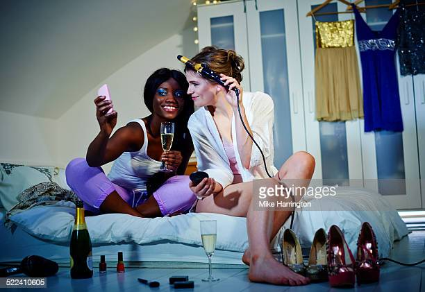 Women getting ready for night out in bedroom