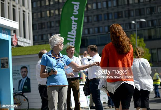 A women gives out electoral leaflets to people advertising the Swedish Moderate Party for the upcoming European Elections in Stockholm on May 25 2014...