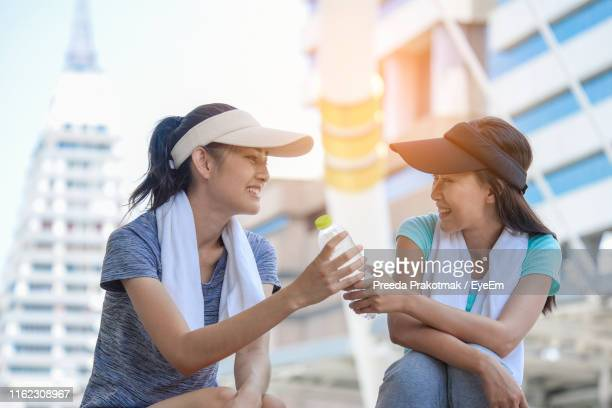 women giving bottle to friend while sitting in city - 手渡す ストックフォトと画像