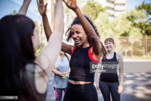 women giving each other high-five after basketball game - deporte de equipo fotografías e imágenes de stock