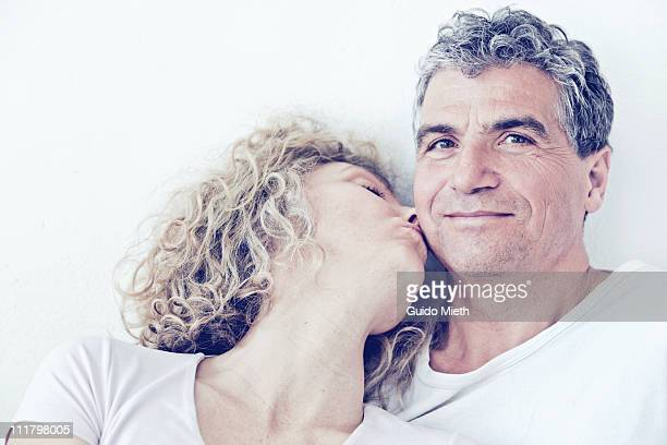 Women giving her husband a kiss on his cheek