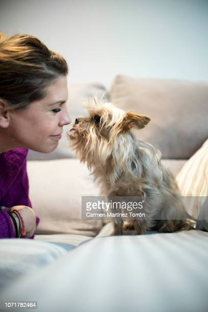 Women giving her pet dog a kiss, vertical shot.