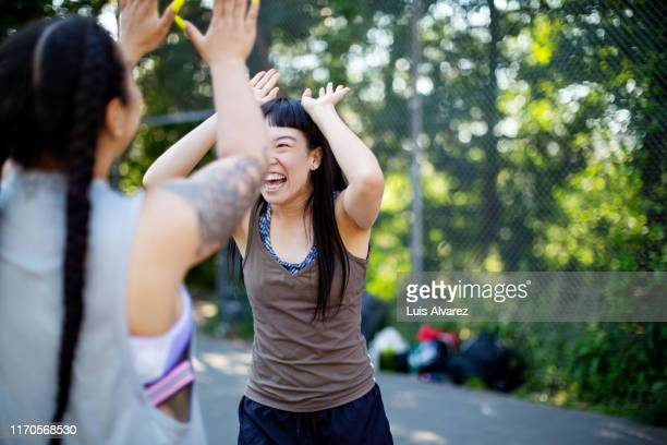 women giving high-five after basketball match - hitting stock pictures, royalty-free photos & images