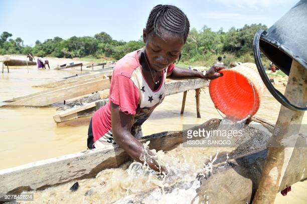 Women gold prospectors work in the Pampana river on March 5 2018 near Mekeni northern Sierra Leone Down a dirt road that slopes off a bridge hundreds...