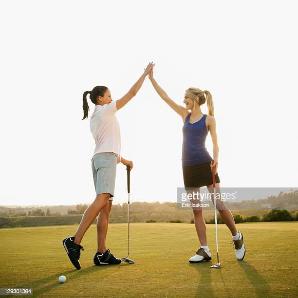 Women golfers high fiving on golf course