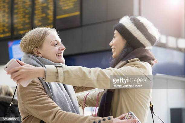 women greeting and embracing eachother at railroad station. - arms outstretched stock pictures, royalty-free photos & images