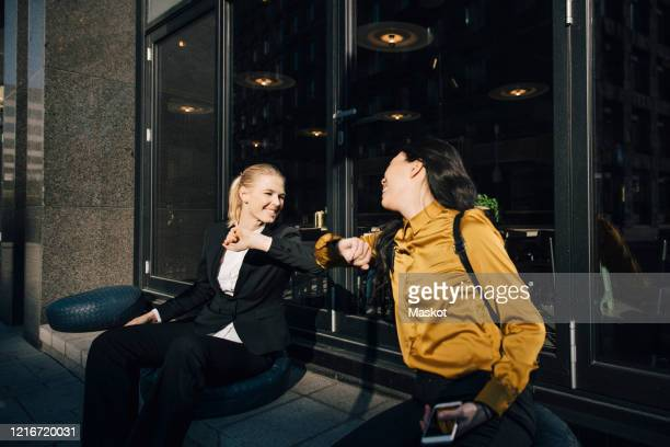 women greeting using elbows - sweden stock pictures, royalty-free photos & images