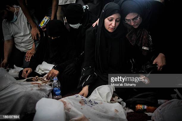 Women grieve next to dead bodies laid at Iman mosque which was turned into a makeshift morgue following the violent dispersal of Rabaa Adaweya square...